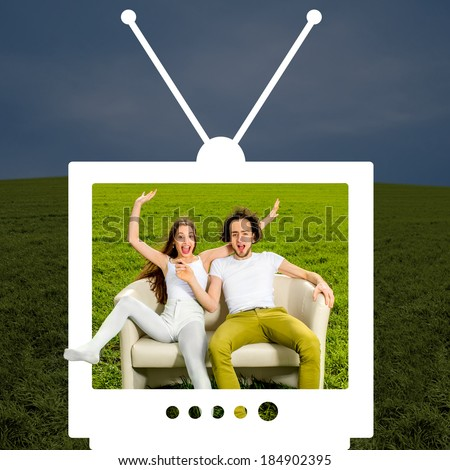 ?razy couple sitting on the couch in the green field looking through the television - stock photo