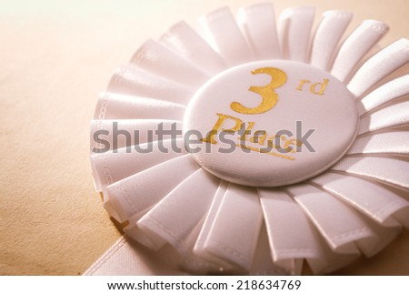 3rd place white winners rosette with gold text made from pleated ribbon, close up view - stock photo