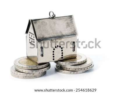 real estate investment on reliable foundation, small silver model house stands on two strong stacks of coins, concept image, isolated on white background with copy space - stock photo