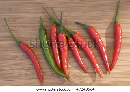 Red and green chillies  on wooden plate - stock photo