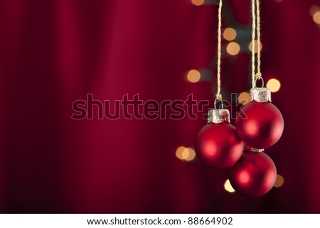3 red baubles on a red and luminous background - stock photo