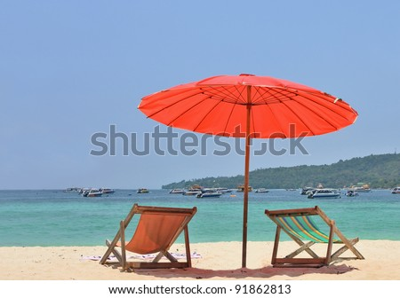Red beach umbrella and deck chairs on the white sand. Tropical paradise on the shores of the azure sea. - stock photo