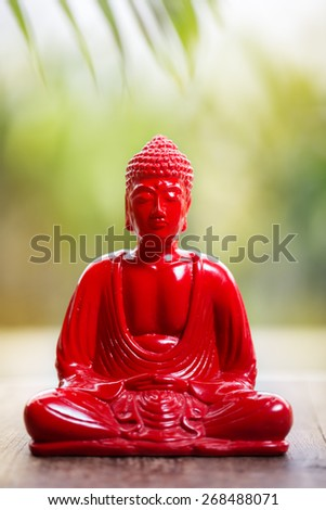 Red Buddha over bright nature background - stock photo