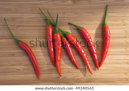 Red  chillies  on wooden plate - stock photo