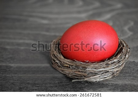 Red Easter egg in a nest on wooden background - stock photo