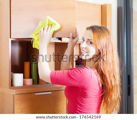 red-haired woman in red cleaning wooden furiture with rag at home - stock photo