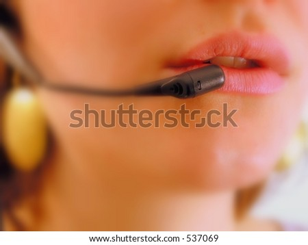 Red lips focused of a girl with headset phone at a call center. - stock photo