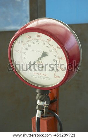 red pressure gauge and checking air pressure of car