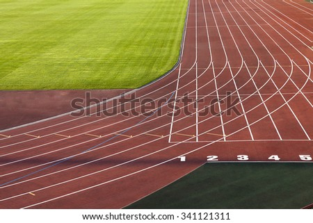 red running track divided by the band. The stadium - stock photo