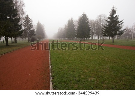 red running track, located in the park in autumn season - stock photo