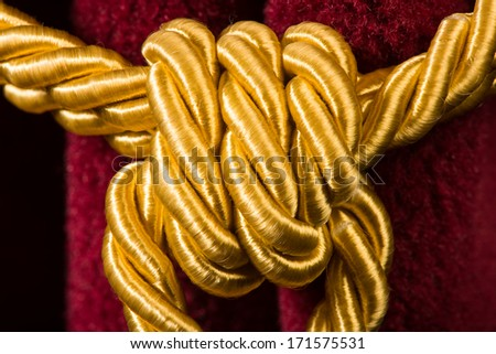 Red velvet curtain with tassel. Close up knot on rope - stock photo