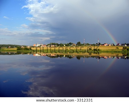 Reflection of a rainbow in water - stock photo