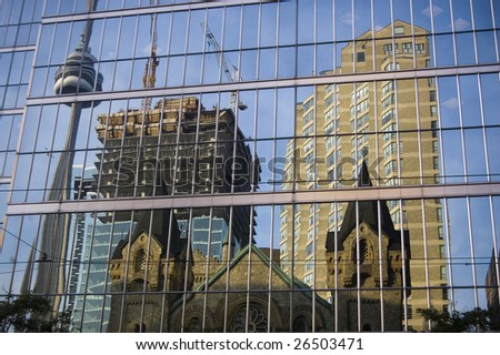 reflection of  cn tower and  construction in  down-town on the glass of  skyscraper - stock photo