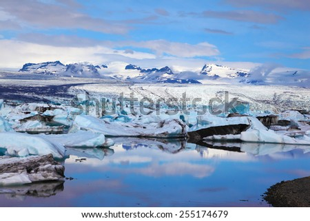 Reflection. Sunrise.  Blue and turquoise icebergs and ice floes are reflected in smooth water of the Gulf J�¶kuls�¡rl�³n in Iceland