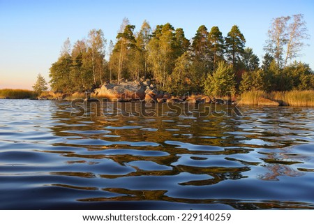reflections in calm waves, rocky island on sunset , Baltic sea                         - stock photo