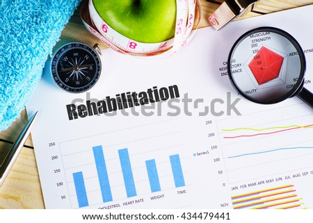 """Rehabilitation"" black text on paper with magnifying glass on red spider bar on wooden table with compass, towel, green apple with measurement tape, and whistles - fitness, diet and healthy concept - stock photo"