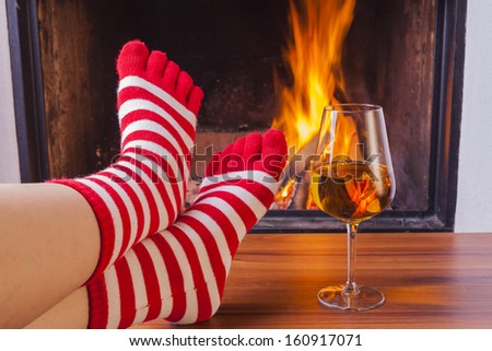 relaxing at fireplace in colorful funny toesocks - stock photo