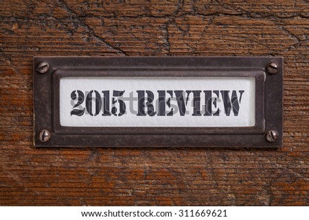 2015 review - a label on wgrunge wooden file cabinet. A passing year summary and review concept. - stock photo