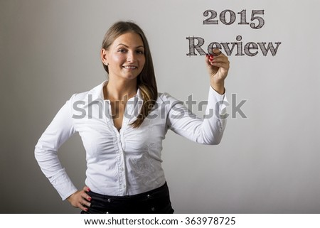 2015 Review  - Beautiful girl writing on transparent surface - horizontal image