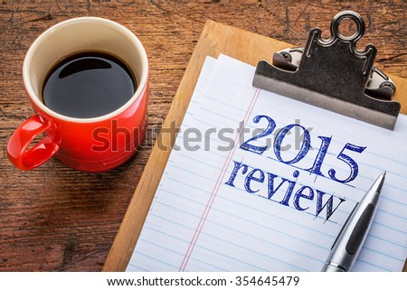 2015 review on clipboard and coffee against grunge wood desk - stock photo