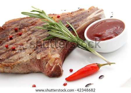Rib-eye steak resting on a white plate - stock photo