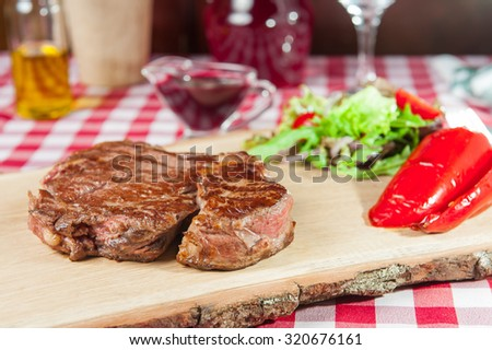 Ribeye steak with vegetable salad pillow, roasted bell pepper  and sauce on the wood board on the  served restaurant table - stock photo
