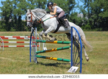 Rider jumping with white horse over obstacle - stock photo