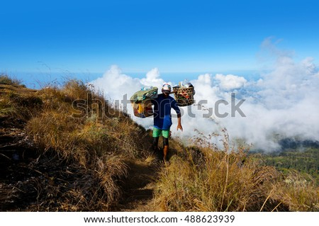 RINJANI MOUNTAIN, LOMBOK, INDONESIA-SEPT 18, 2016: Unidentified mountain porter carries food necessities walks slowly on trekking path on Plawangan Sembalun to Rinjani Mountain in Lombok, Indonesia.