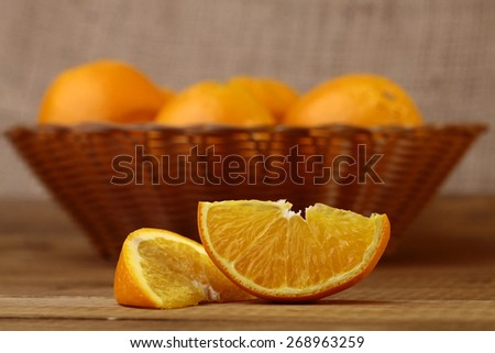 Ripe orange fruits in basket and orange slices on wooden table - stock photo