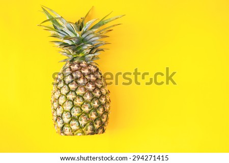 Ripe whole pineapple isolated on yellow background - stock photo