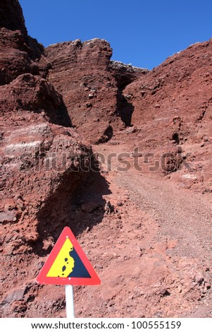 """""""Risk of Falling or Fallen Rocks"""" warning sign against red cliffs - stock photo"""