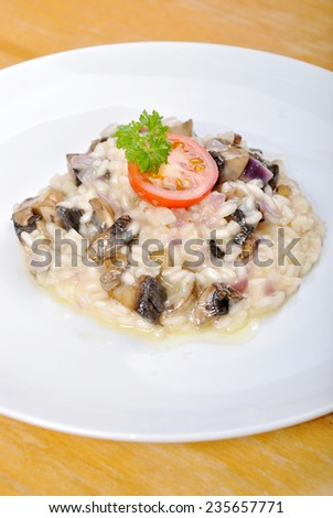 Risotto with champignon mushrooms,shallot and fresh cherry tomato on the wooden desk - stock photo