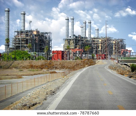 road leading to industrial factory with smokestacks and cloudy sky - stock photo