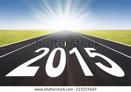 2015 road perspective with rising sun - stock photo