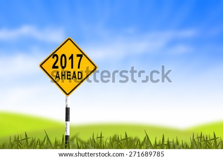 2017, Road sign in the grass field to new year and blue sky, can use as abstract background - stock photo