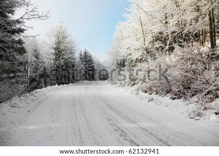 Road to a snow. Solar winter morning in a wood. - stock photo
