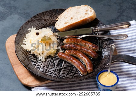 4 roasted Nuremberger Bratwurst/Sausages with Sauerkraut, Mustard and Bread in an iron Pan on a wooden board. - stock photo