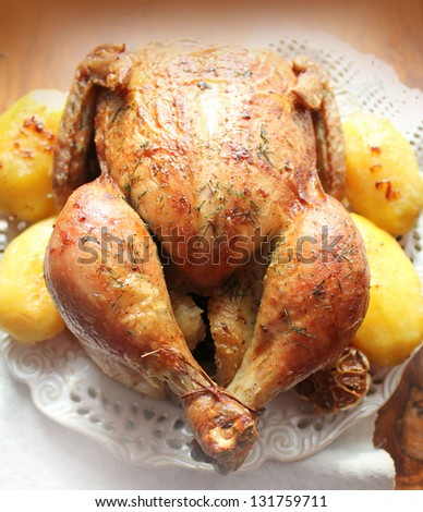 Roasted whole chicken with potatoes  - stock photo