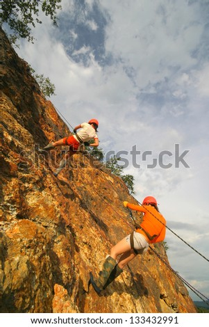 rock climber climbing an overhanging cliff against the blue sky - stock photo