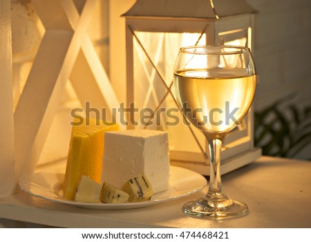 Romantic background with a glass of wine, cheese and retro lamp. selective focus