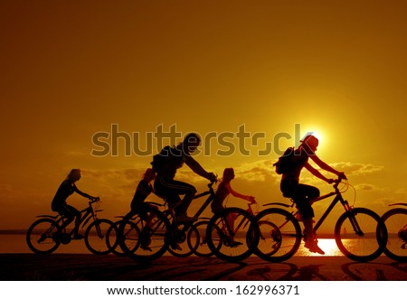 3 romantic couples cyclists ride towards each other silhouette in sunrise against sun set cloudy sky and sea shore background Space for inscription