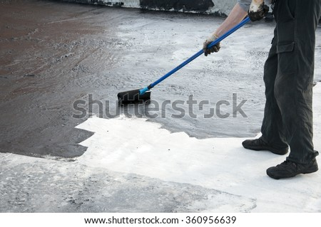 Roofer worker painting   the roller brush,  for waterproofing. - stock photo