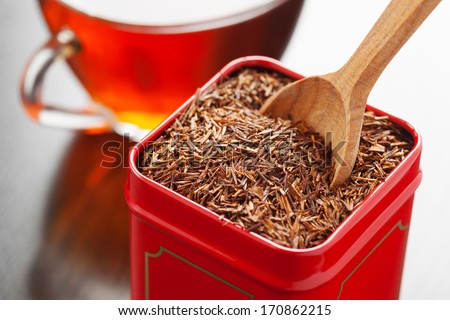 rooibos in tea tin box and wooden spoon closeup - stock photo