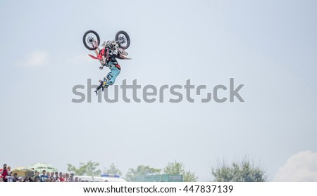 """Rostov-on-Don, Russia- June 05,2016: The athlete performs a jump on a motorcycle in the competition of tractors called """"Bison Track Show"""" - stock photo"""