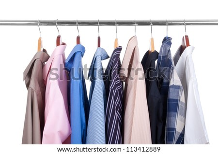 row of colorful row shirts hanging on hangers on a white background - stock photo