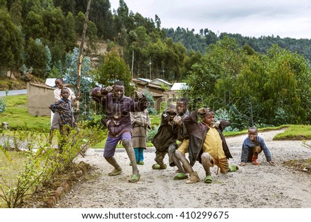 RUHENGERI, RWANDA - SEPTEMBER 7, 2015: Unidentified children. The curious four. When they see the strangers and their cameras, they watch around in curiosity and astonishment.