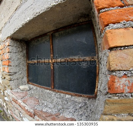 Ruined rustic limestone boulder rubble wall masonry stonework ruins and red brick window aperture opening weathered old aged wooden frame - stock photo