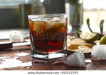RUM , coctail cuba libra, rum and cola cuba libre with lime and Ice into the glass beaker closeup