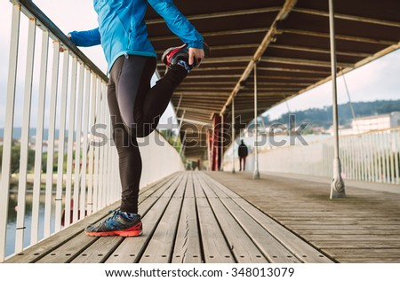 Runner man doing stretching leaning against the railing of a bridge outdoors - stock photo