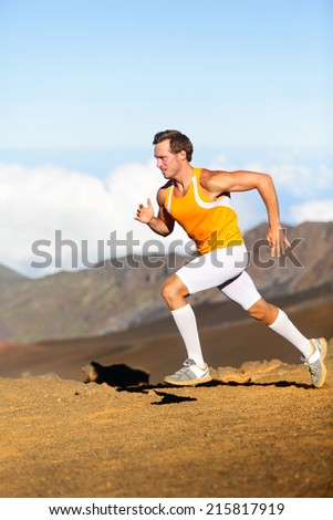 Running man on cross country trail run marathon in beautiful landscape nature. - stock photo